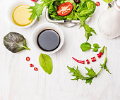Salad preparation with oil and balsamic vinegar on white wooden table
