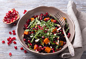 Salad with black rice, baked pumpkin, pomegranate seeds, arugula and nuts on a gray background. Delicious vegan food