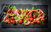 Salad with ham jamon serrano, cherry tomatoes, arugula on black stone slate board, grey background. Top view