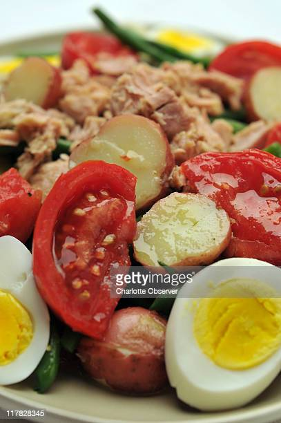 Salade Nicoise is made more elaborate with potatoes green beans onions tomatoes and black olives Instead of tuna it might have bacon cold meat or no...