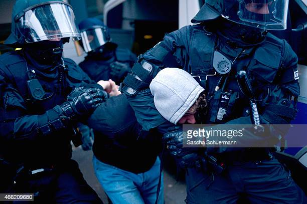 Salafi counter demonstrator is tackled by riot police forces during a rally of Pegida on March 14 2015 in Wuppertal Germany Several hundred Salafis...