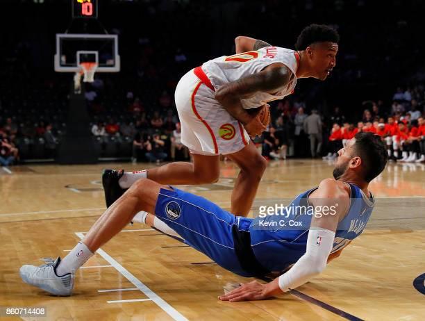 Salah Mejri of the Dallas Mavericks falls as John Collins of the Atlanta Hawks drives the basket at McCamish Pavilion on October 12 2017 in Atlanta...