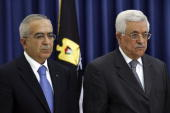 Salam Fayad the new Palestinian Prime Minister stands alongside Palestinian President Mahmoud Abbas as Abbas swears in the new government on June 17...