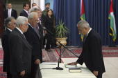 Salam Fayad the new Palestinian Prime Minister swears an oath of allegiance on the Quran in front of Palestinian President Mahmoud Abbas and other...