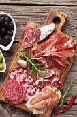Salami, sliced ham, sausage, prosciutto, bacon, toasts, olives. Meat antipasto platter on wooden table. Top view