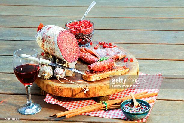 Salami on chopping board with wine and condiments