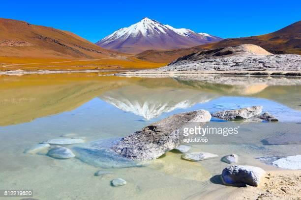 Salar de Talar and Miniques snowcapped Volcano - Turquoise lake mirrored reflection and Piedras rojas (red stones) rock formation at sunrise, Idyllic Atacama Desert, Volcanic landscape panorama – San Pedro de Atacama, Chile, Bolívia and Argentina border
