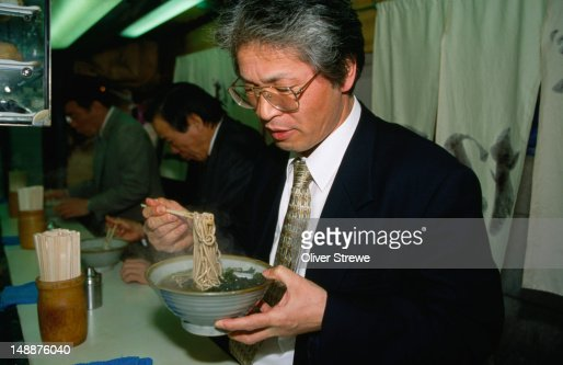 A 'salaryman' at a stand-up soba restaurant, eating tempura soba (buckwheat) in Osaka. The term salaryman describes the private and working lives of Japan.