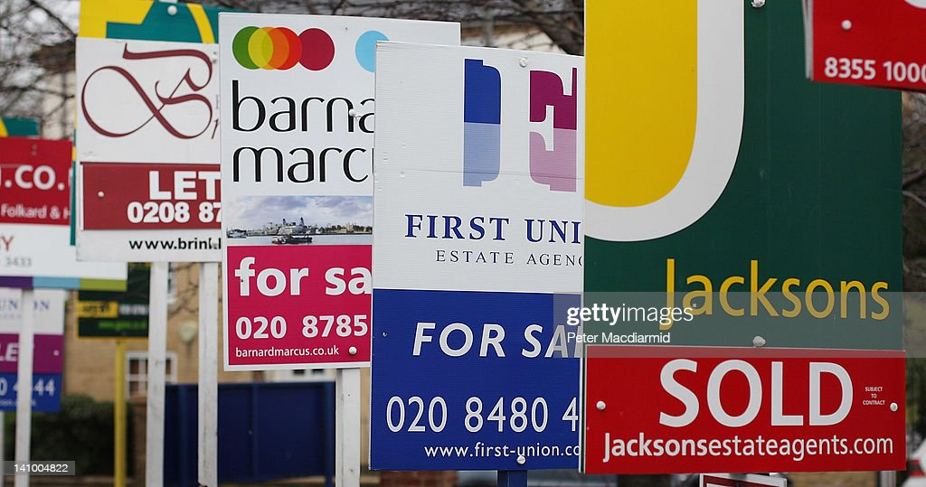 Sale and rent signs are displayed by estate agents on a block of flats near Wandsworth on March 7, 2012 in London.