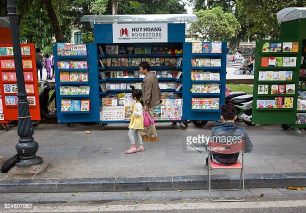 Sale of books on mobile sales stall on a street in Hanoi In the foreground a young man sits on a chair on October 30 2016 in Hanoi Vietnam