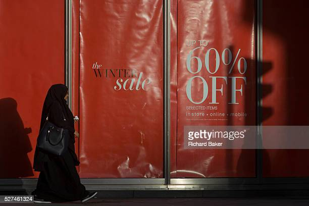 Sale reductions at a branch of UK retailer Marks Spencer on Bishopsgate in the City of London With the shadow of a nearby traffic light a Muslim lady...