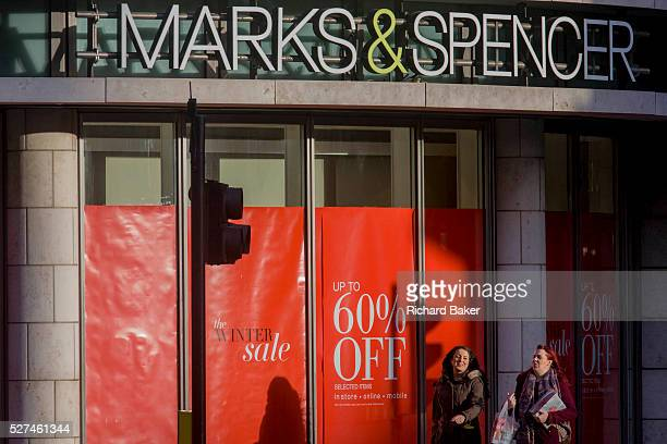 Sale reductions at a branch of UK retailer Marks Spencer on Bishopsgate in the City of London With their own shadows two women consumers walk past...