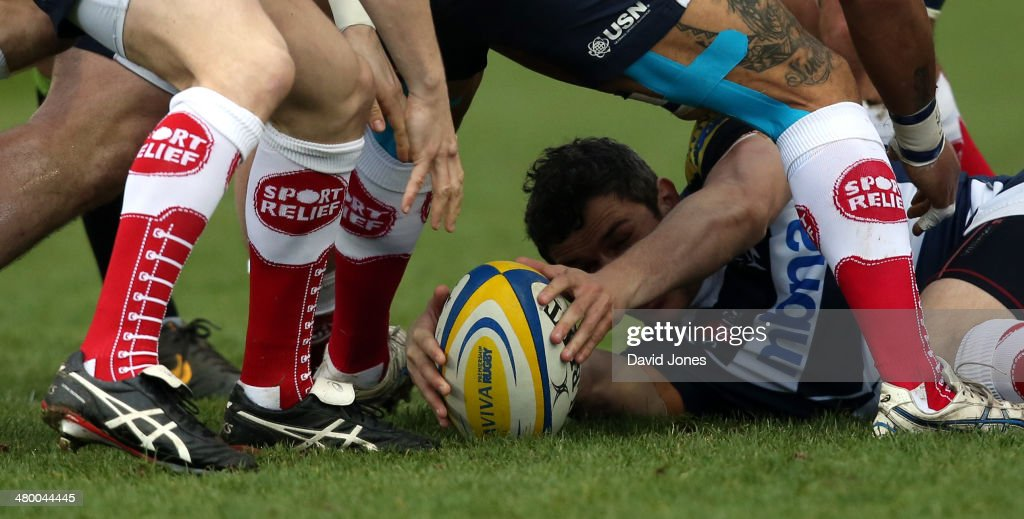 Sale Sharks players wearing Sport Relief socks surround Tom Brady of Sale Sharks as he places the ball after a tackle during the Aviva Premiership match between Sale Sharks and Northampton Saints at A J Bell Stadium on March 22, 2014 in Salford, England