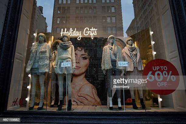 A sale sign is displayed next to mannequins in the window of a Hennes Mauritz AG store in the SoHo neighborhood of New York US on Friday Dec 5 2014...