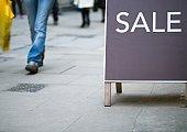 Sale sign, shopper walking by