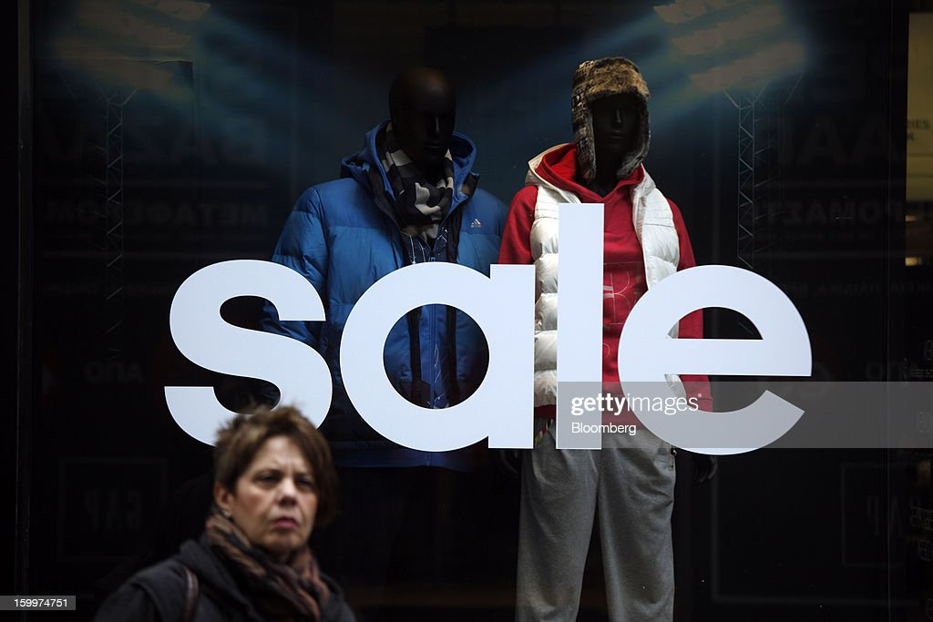 A sale sign sits in the window of a fashion store in Athens, Greece, on Thursday, Jan. 24, 2013. Greece's government has implemented budget cuts and economic reforms to tame a fiscal deficit that has led to bailouts from the European Union and the International Monetary Fund. Photographer: Kostas Tsironis/Bloomberg via Getty Images