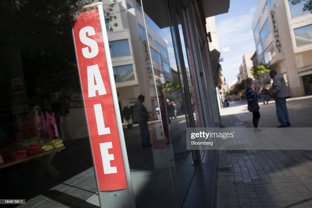 A sale sign sits in the window of a retail store in Nicosia, Cyprus, on Monday, March 25, 2013. In a replay of tensions over aid for Greece at the outset of the crisis, European governments had wrangled over aid for Cyprus for nine months, exposing holes in the revamped economic management system that was built in three years of emergency policymaking, often at all-night summits. Photographer: Photographer: Simon Dawson/Bloomberg via Getty Images