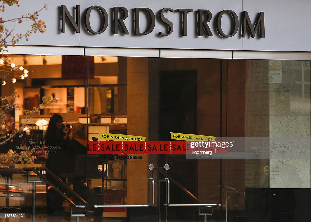 'Sale' signs are displayed on doors as a customer has make-up applied inside a Nordstrom Inc. department store in Santa Monica, California, U.S., on Tuesday, Nov. 12, 2013. Nordstrom Inc. is scheduled to release earnings figures on Nov. 14. Photographer: Patrick T. Fallon/Bloomberg via Getty Images