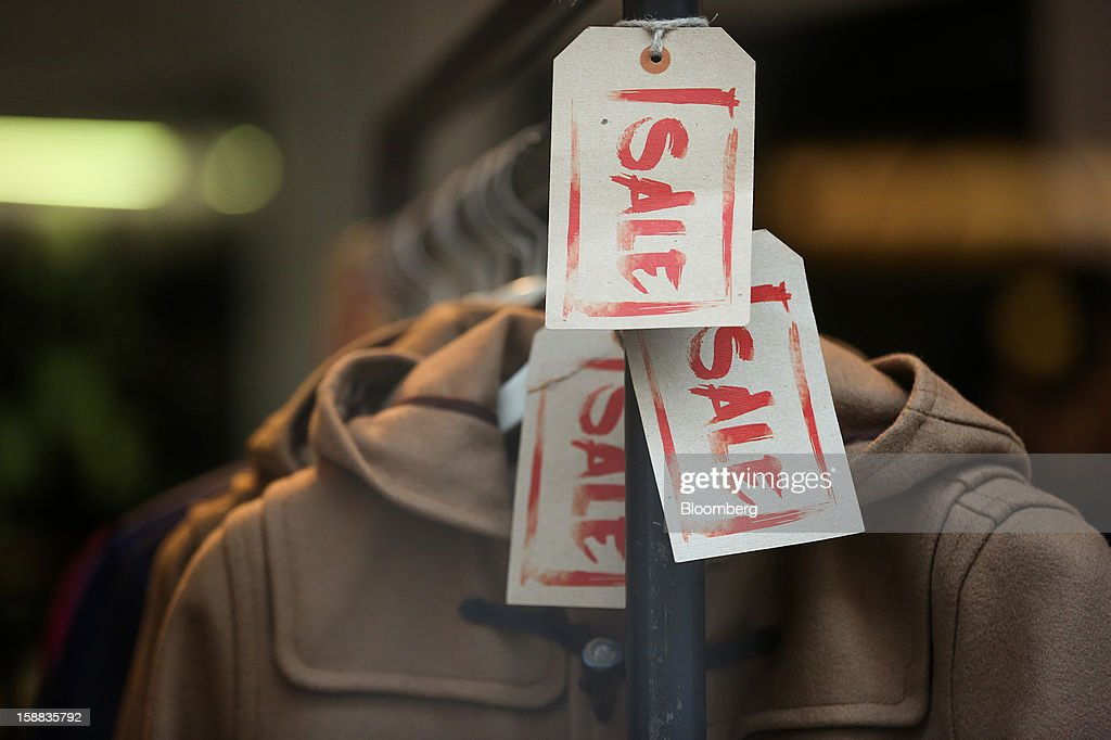 Sale signs are seen on a display of duffel coats in a Fred Perry Ltd. clothing store in the Covent Garden district of London, U.K., on Monday, Dec. 31, 2012. The number of Britons making shopping trips for post-holiday bargains barely increased on the day after Christmas as more people sought discounts online. Photographer: Jason Alden