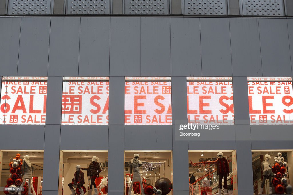 Sale signs hang above Uniqlo Co. Ltd. store's Christmas windows on Fifth Avenue in New York, U.S., on Sunday, Dec. 23, 2012. Holiday shoppers descended on U.S. stores this weekend in a last-minute dash to buy gifts amid concerns about the nation's economy and the impasse in Washington over taxes and spending. Photographer: Victor J. Blue/Bloomberg via Getty Images