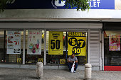 Sale signs hang in the windows of a store a day after Puerto Rican Governor Alejandro Garcia Padilla gave a televised speech regarding the...