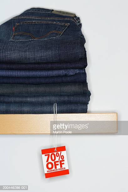 Sale tag attached to jeans piled on shelf display, close-up