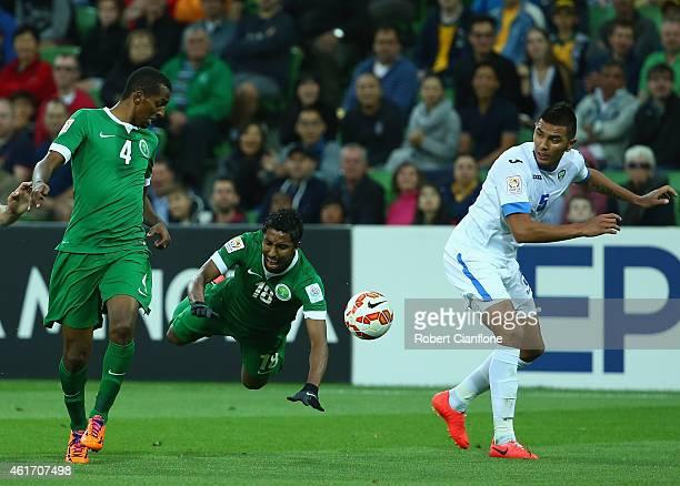 Salem Aldawsari of Saudi Arabia is fouled by Anzur Ismailov of Uzbekistan during the 2015 Asian Cup match between Uzbekistan and Saudi Arabia at AAMI...