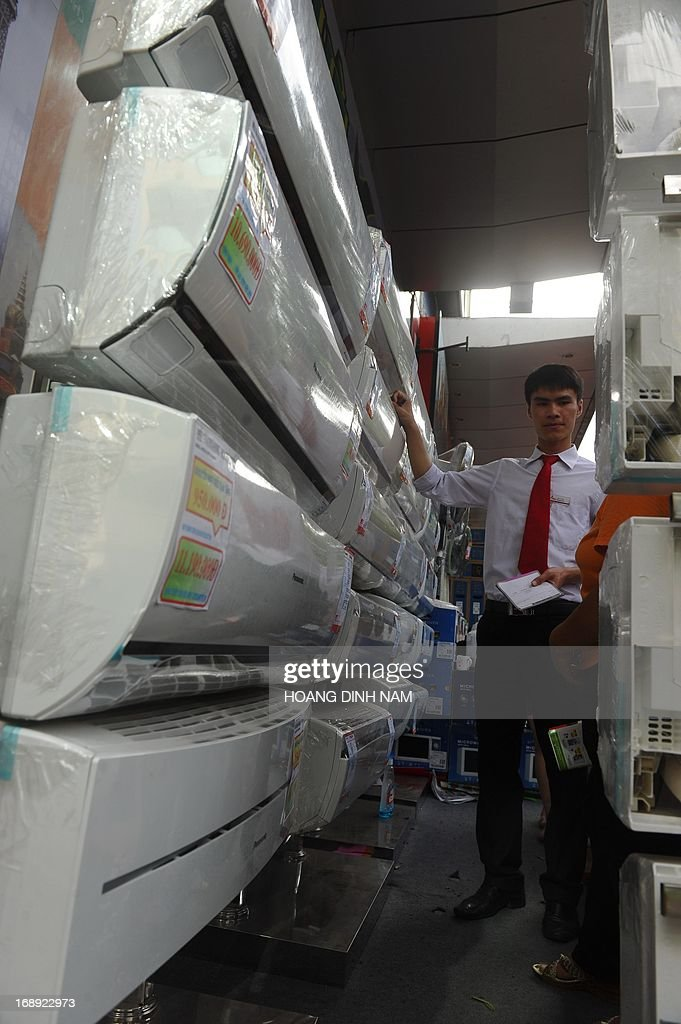 A saleman (L) helps a customer choosing an air conditionners at an electrical store in downtown Hanoi on May 17, 2013. The demand for air conditioners rose up since the country is facing the first severe heat wave at the beginning of this summer which is expected to be hard this year according to weather forecast reports. AFP PHOTO/HOANG DINH Nam