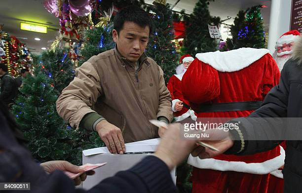 A saleperson looks at a customer buying Christmas decorations at a market on December 19 2008 in Beijing China A large number of Christmas...