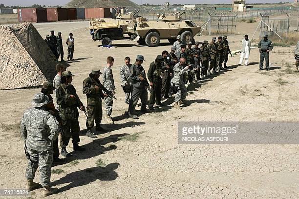 A US military police from 546 company 3rd platoon teaches Afghan police officers the position they should take to shoot with their weapons during a...