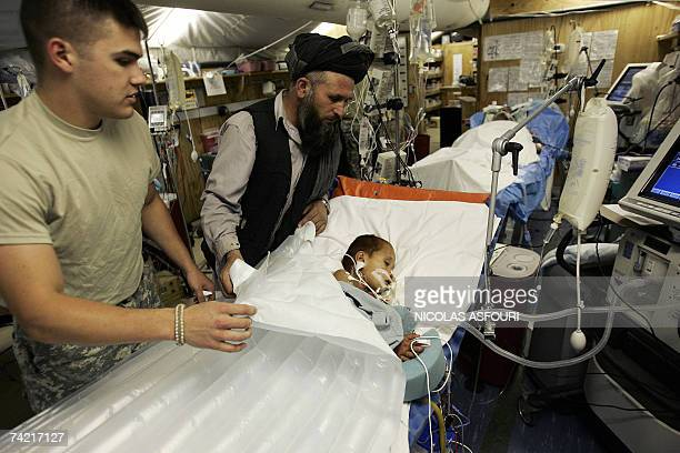 Task force med Seargent Greg Wulczy pulls back the covers to show Afghan boy Azada Khan who was seriously injured after a Taleban mortar attack on...