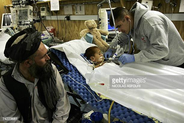 Task force medical Seargent Greg Wulczy examines Afghan boy Azada Khan who was seriously injured after a Taleban mortar attack on May 14 in Khost...