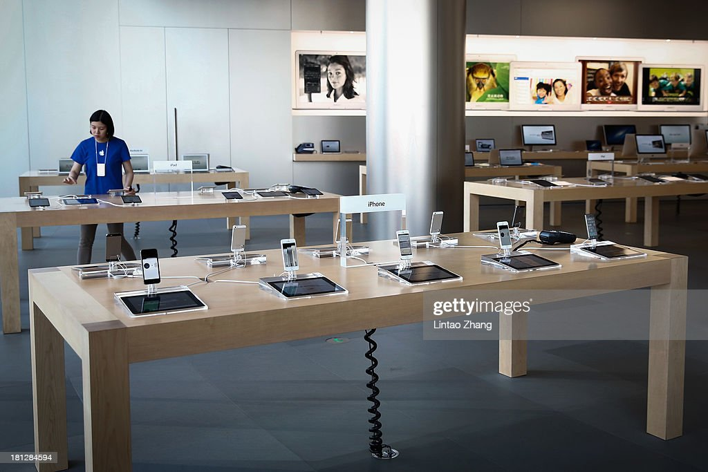 A sales assistant arranges new Apple iPhone 5s smartphones at the Wangfujing flagship store on September 20, 2013 in Beijing, China. Apple launched the new iPhone 5C model that will run iOS 7 is made from hard-coated polycarbonate and comes in various colors and the iPhone 5S that features fingerprint recognition security.