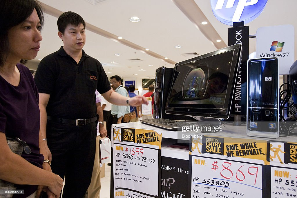 A sales assistant demonstrates a computer for sale in a store in Singapore, on Monday, May 24, 2010. Singapore's consumer prices rose at the fastest pace in 14 months in April as an accelerating economy and a booming labor market boosted housing and transportation costs. Photographer: Charles Pertwee/Bloomberg via Getty Images