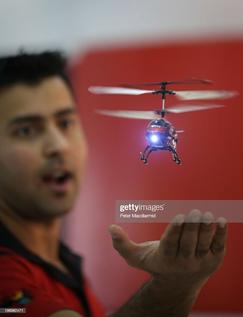 A sales assistant demonstrates a toy helicopter at The Ideal Home Christmas Show on November 14, 2012 in London, England. Over 400 exhibitors are showcasing a range of gift ideas for Christmas at the Earls Court exhibition centre.