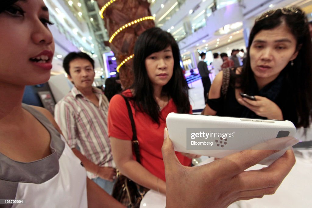 A sales assistant demonstrates the BlackBerry Z10 smartphone to customers during the consumer launch of the device at the Central Park Mall in Jakarta, Indonesia, on Friday, March 15, 2013. BlackBerry, the Canadian smartphone maker that rolled out a new lineup in January, said one of its 'established partners' is buying 1 million BlackBerry 10 phones, the biggest order in the company's history. Photographer: Dimas Ardian/Bloomberg via Getty Images