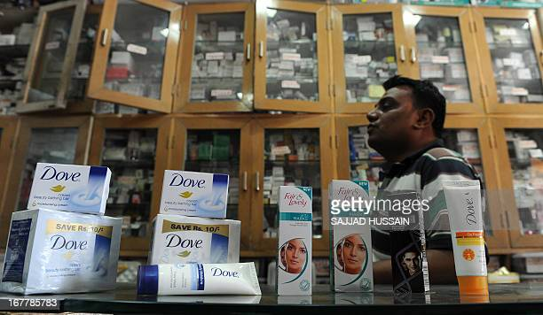 A sales assistant displays Unilever products Fair and Lovely skin fairness cream and Dove soap at a shop in New Delhi on April 30 2013 Food giant...