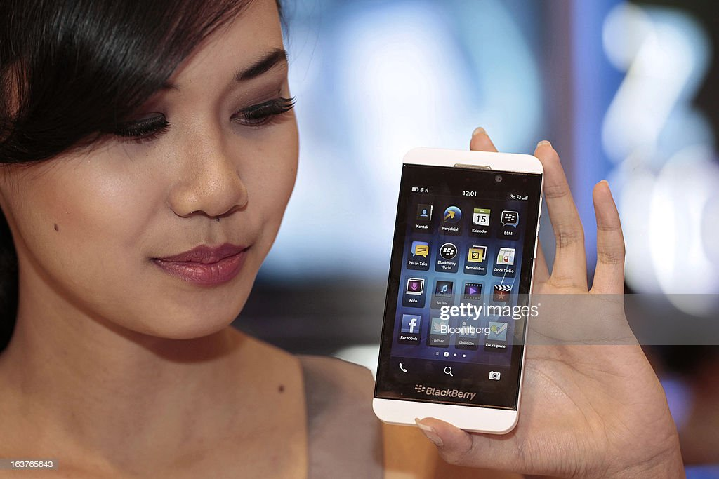 A sales assistant holds the BlackBerry Z10 smartphone for a photograph during the consumer launch of the device at the Central Park Mall in Jakarta, Indonesia, on Friday, March 15, 2013. BlackBerry, the Canadian smartphone maker that rolled out a new lineup in January, said one of its 'established partners' is buying 1 million BlackBerry 10 phones, the biggest order in the company's history. Photographer: Dimas Ardian/Bloomberg via Getty Images