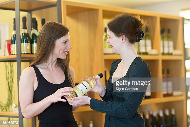 Sales assistant in wine shop recommending bottle of wine to customer