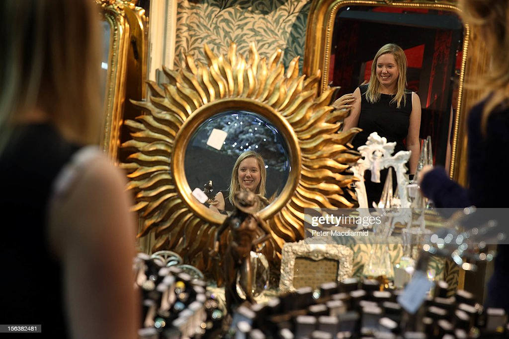 A sales assistant is reflected in ornate mirrors at The Ideal Home Christmas Show on November 14, 2012 in London, England. Over 400 exhibitors are showcasing a range of gift ideas for Christmas at the Earls Court exhibition centre.