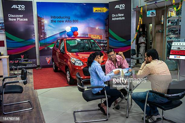 A sales assistant left attends to customers in a Maruti Suzuki India Ltd dealership in New Delhi India on Thursday Oct 25 2012 With only 13 percent...