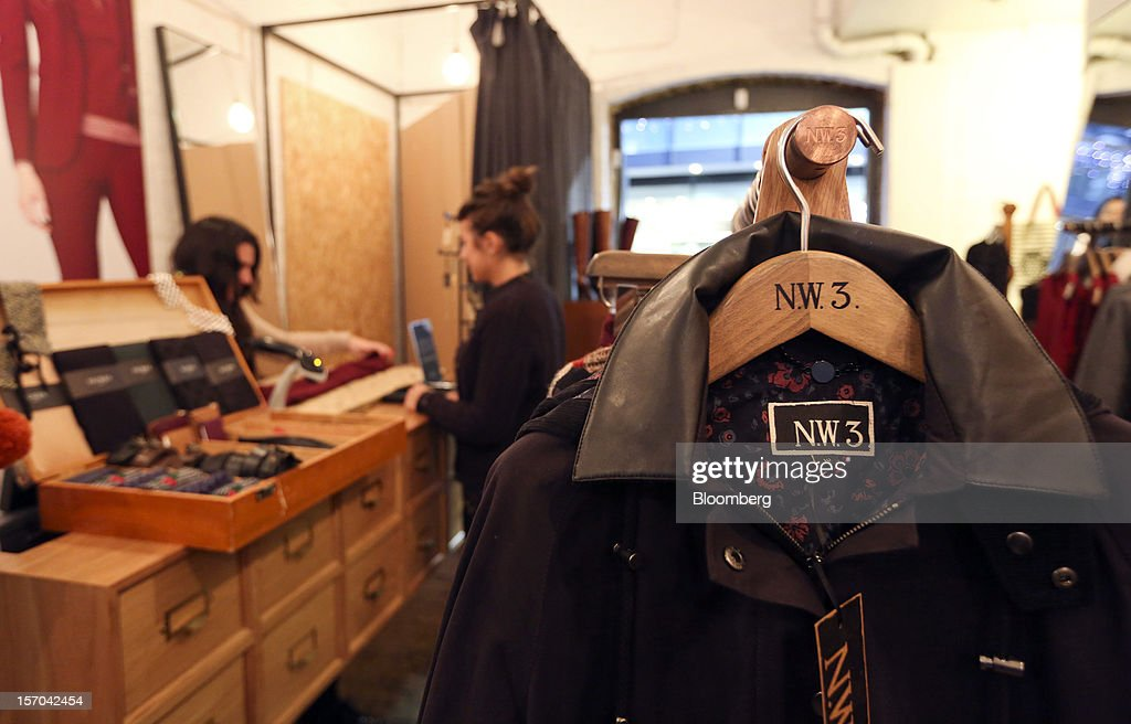 A sales assistant, left, serves a customer, center, inside a NW3 store, a brand of Hobbs and former pop-up store, in London, U.K., on Tuesday, Nov. 27, 2012. Fashion chain Hobbs is among those that have opened pop-up stores for the first time this year, while CD and DVD retailer HMV Group Plc is adding more than usual for the holiday in an effort to win business. Photographer: Chris Ratcliffe/Bloomberg via Getty Images