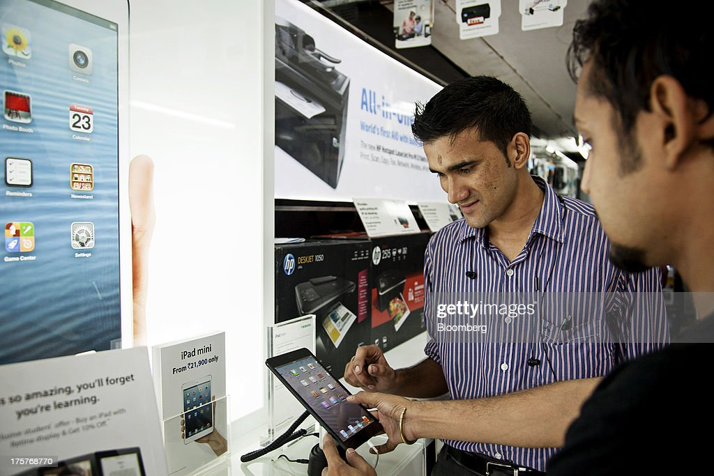 A sales assistant, left, shows an Apple Inc. ipad mini to a customer at a store in Nehru Place IT Market, a hub for the sale of electronic goods and computer accessories, in downtown New Delhi, India, on Wednesday, Aug. 7, 2013. India's consumer price index (CPI) figures for July are scheduled to be released on August 12. Photographer: Graham Crouch/Bloomberg via Getty Images