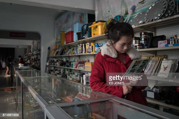 A sales assistant looks at a leaflet as she waits for customers at a vehicle parts shop in Pyongyang on November 16 2017 / AFP PHOTO / Ed JONES