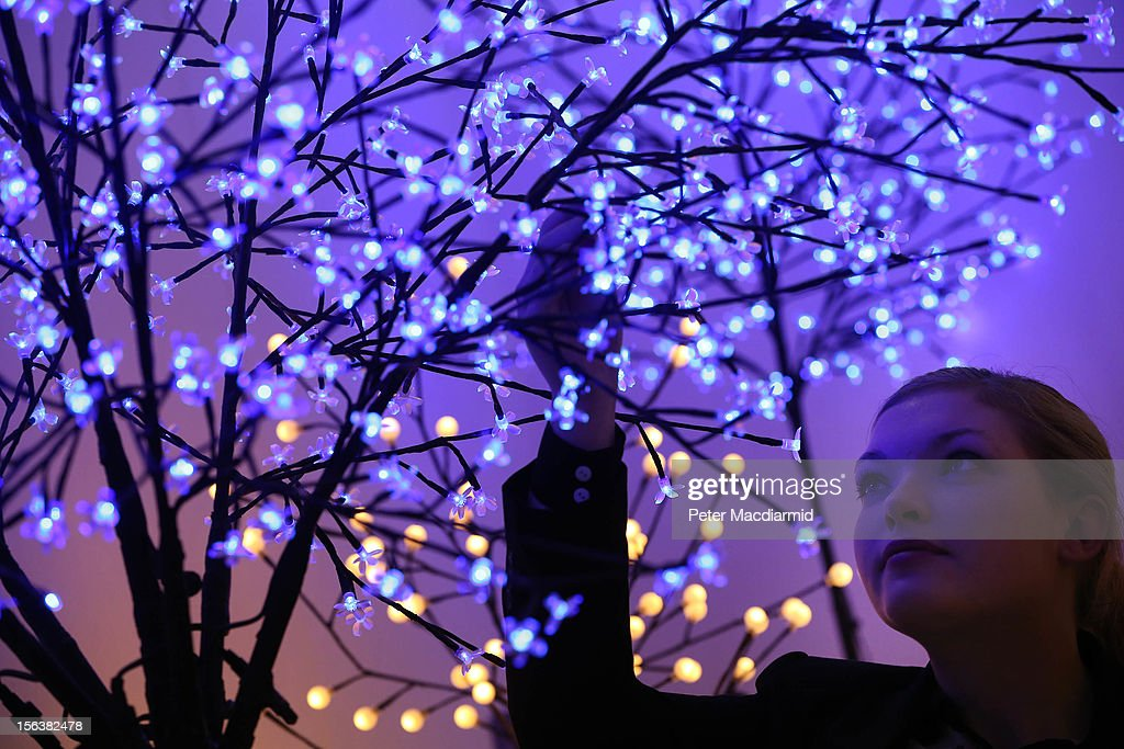 A sales assistant looks up at Christmas tree lights on display at The Ideal Home Christmas Show on November 14, 2012 in London, England. Over 400 exhibitors are showcasing a range of gift ideas for Christmas at the Earls Court exhibition centre.