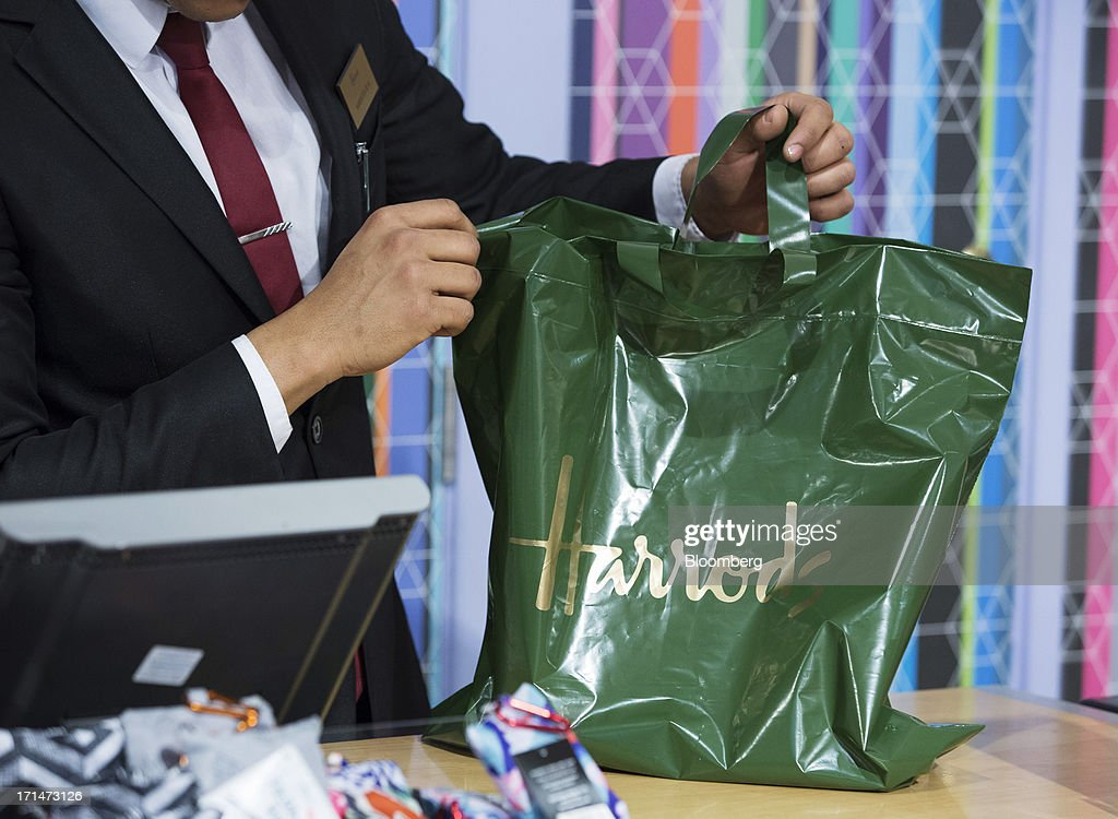 A sales assistant passes a bag to a customer inside Harrods luxury department store in this arranged photograph in London, U.K., on Monday, June 24, 2013. Harrods, which has more than 1 million square feet (90,000 square meters) of selling space, isn't concerned about the outlook for spending on luxury goods, Harrods Managing Director Michael Ward said. Photographer: Jason Alden/Bloomberg via Getty Images