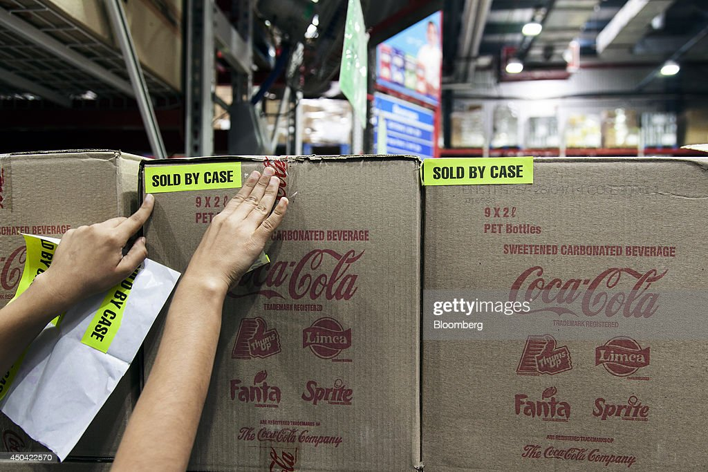 A sales assistant places a 'Sold By Case' sticker onto a box of Coca-Cola Co. beverages at a Walmart India Pvt. Best Price Modern Wholesale store in the town of Zirakpur on the outskirts of Chandigarh, Punjab, India, on Tuesday, June 10, 2014. India's consumer price index (CPI) figures and wholesale price inflation figures for May are scheduled for release on June 12 and 16 respectively. Photographer: Udit Kulshrestha/Bloomberg via Getty Images