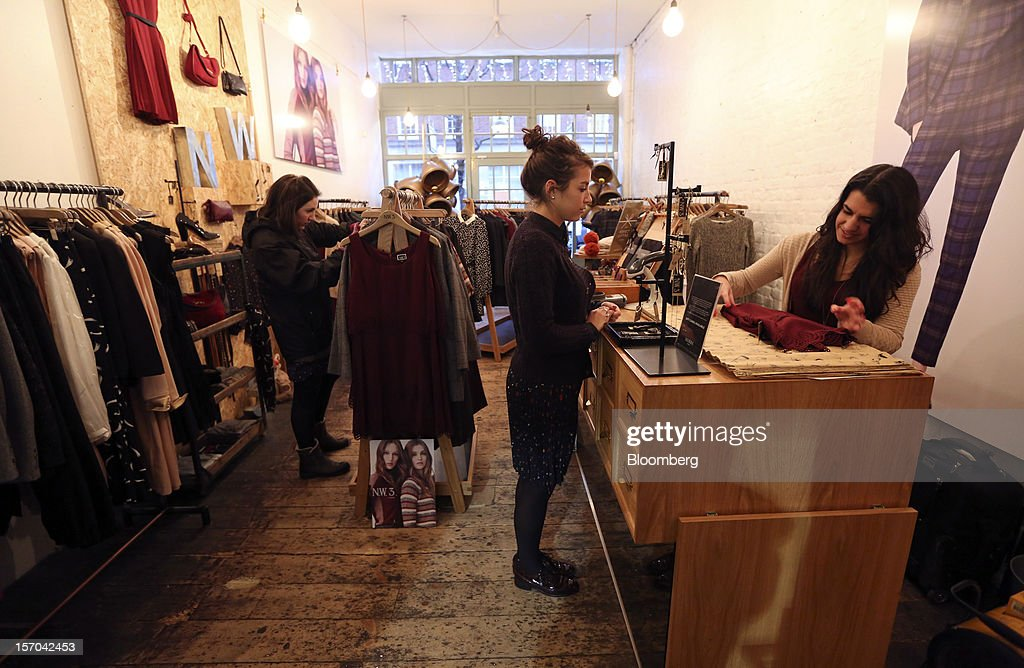 A sales assistant, right, serves a customer, center, inside a NW3 store, a former pop-up store and brand of Hobbs, in London, U.K., on Tuesday, Nov. 27, 2012. Fashion chain Hobbs is among those that have opened pop-up stores for the first time this year, while CD and DVD retailer HMV Group Plc is adding more than usual for the holiday in an effort to win business. Photographer: Chris Ratcliffe/Bloomberg via Getty Images