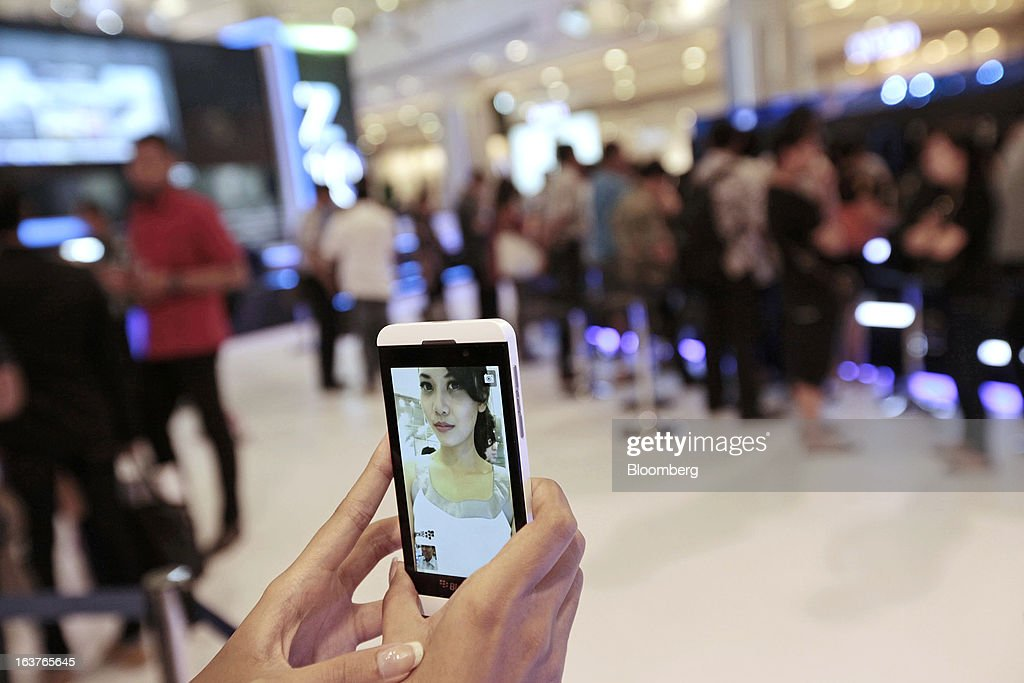 A sales assistant takes a photograph of herself with the BlackBerry Z10 smartphone during the consumer launch of the device at the Central Park Mall in Jakarta, Indonesia, on Friday, March 15, 2013. BlackBerry, the Canadian smartphone maker that rolled out a new lineup in January, said one of its 'established partners' is buying 1 million BlackBerry 10 phones, the biggest order in the company's history. Photographer: Dimas Ardian/Bloomberg via Getty Images