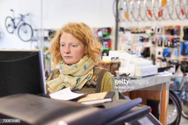 Sales assistant using computer in bike shop